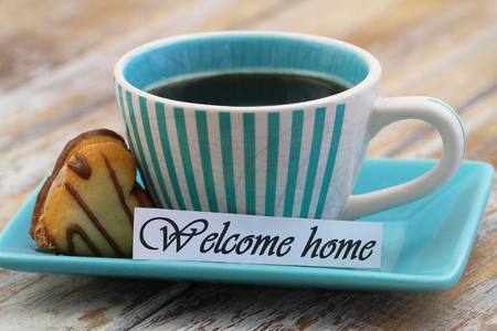 welcome home: Welcome home card with cup of black coffee and heart shaped biscuit