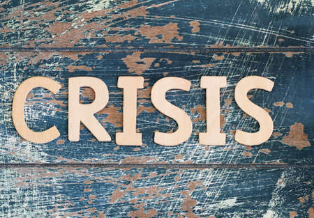 global crisis: Word crisis written on rustic wooden surface