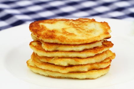 stacked up: Potato fritters stacked up on white plate Stock Photo