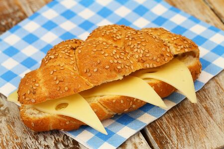 challah: Sesame seed challah sandwich with cheese on checkered paper napkin