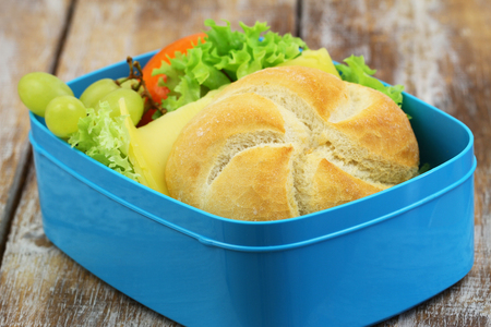 mandarine: Lunch box containing bread roll with cheese and lettuce, grapes and mandarine closeup