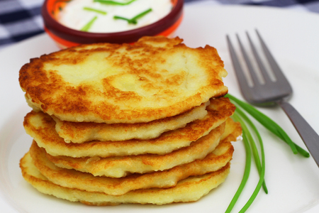 Stack of golden potato fritters on white plate