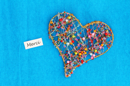 Merci (Which Means thank you in French) card with heart made of colorful beads on blue background
