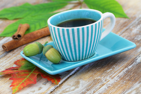 stripy: Black coffee in vintage stripy cup, acorns and cinnamon sticks on rustic wooden surface