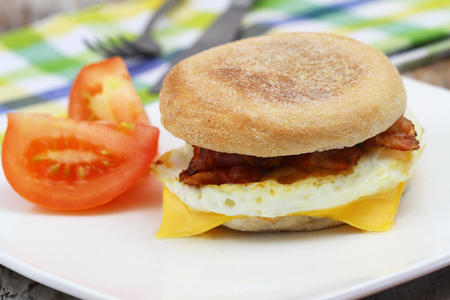 Egg and bacon muffin on white plate