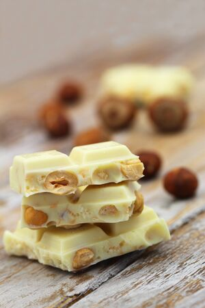 White chocolate with whole hazelnuts stacked up on rustic wooden surface Stock Photo