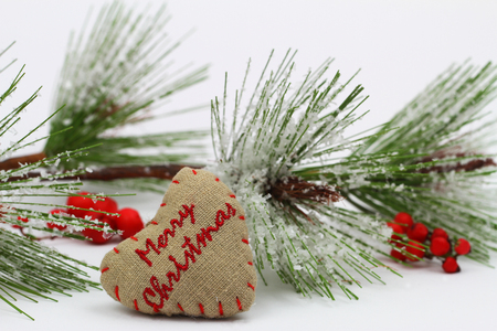 Merry Christmas written on canvas heart and pine covered with snow flakes