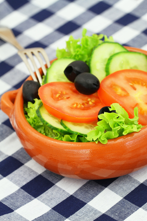 Bowl of salad consisting of lettuce, tomatoes, cucumber and black olives on checkered cloth Stock Photo