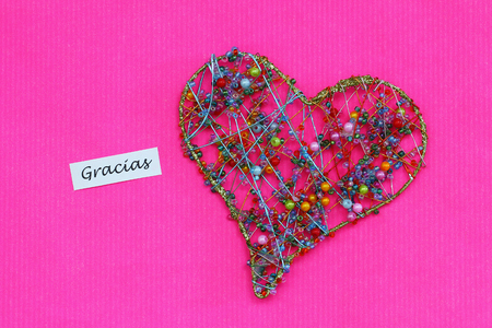 Gracias (thank you in Spanish) card with heart made of colorful beads on pink surface