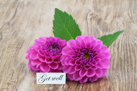 Get well card with pink dahlia flowers on wooden surface Stock Photo
