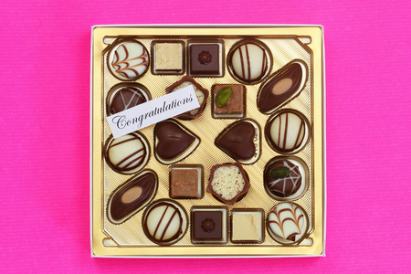 Congratulations card with box or assorted milky, white and dark chocolates on pink background