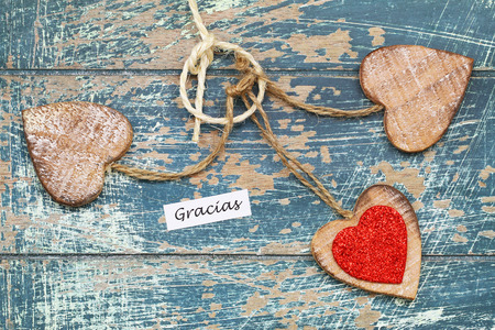 Gracias (which means thank you in Spanish) with wooden hearts on rustic wooden surface Stock Photo