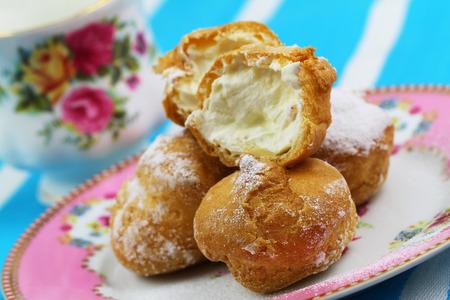 Profiterole dessert with fresh whipped cream, close up