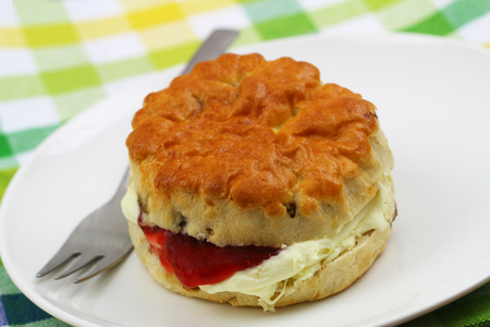 Freshly baked English scone with traditional clotted cream and strawberry jam on white plate, closeup