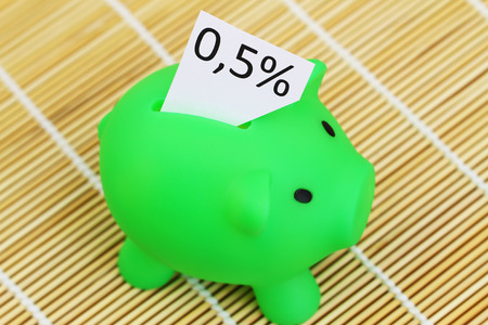 Piggy bank with note showing 0.5% interest rate sticking out of it