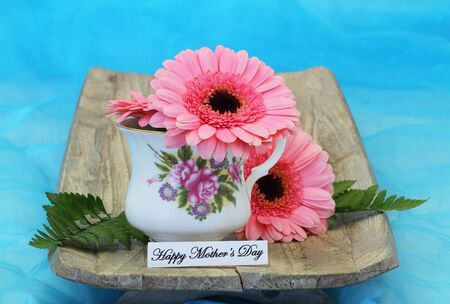 Happy Mother's Day card with pink gerbera daisies in vintage porcelain cup Standard-Bild - 133965766