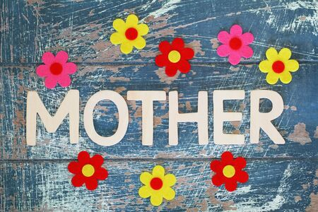 Word mother written with wooden letters on rustic surface with colorful flowers Standard-Bild - 133965831