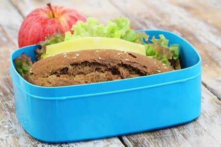 Packed lunch box containing brown cheese sandwich and red apple on rustic wooden surface