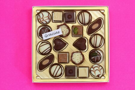Gracias (which means thank you in Spanish) card with box or assorted chocolates on pink background Stock fotó