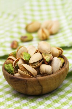 Pistachios in small wooden bowl on green and white checkered cloth, closeup