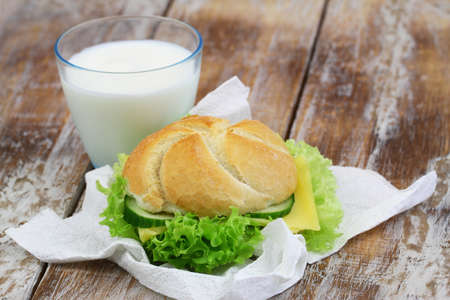 Simple lunch consisting of cheese roll with lettuce and glass of milk Stock Photo