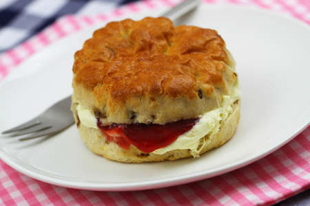 Home made English scone with traditional clotted cream and strawberry jam on white plate, closeup Stock Photo