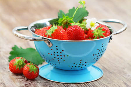 Fresh strawberries in blue colander on wooden surface Stock Photo