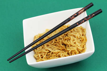 Chinese noodles in bowl and chopsticks on green background