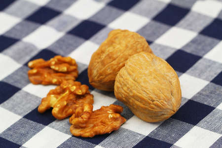 Walnuts with and without a shell on a checkered cloth, closeup