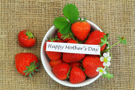 Happy Mother's Day card with bowl of fresh strawberries on burlap background Stock Photo