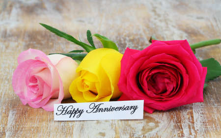 Happy Anniversary card with three colorful roses on rustic wooden surface Stock Photo