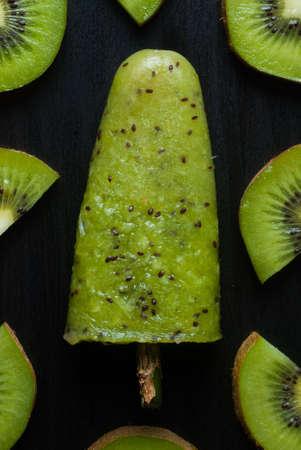 helados con palito: ice lolly with kiwi on a dark background Foto de archivo