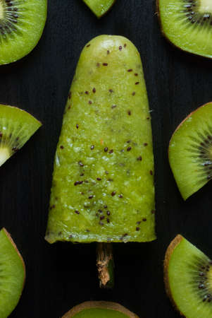 helados con palito: polo de hielo con el kiwi en un fondo oscuro