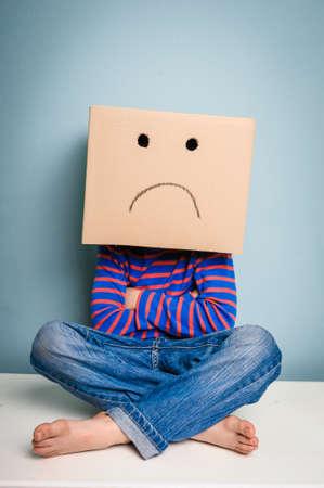 persona deprimida: niño gruñón infeliz con la caja de cartón sobre la cabeza Foto de archivo