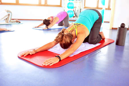inddor: Two women doing yoga at fitness gym Stock Photo