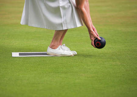 wood lawn: A mature lady player playing lawn bowls. Stock Photo