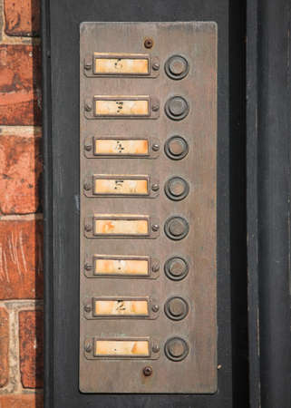 Row of numbered door bell buttons on a wall Stock Photo