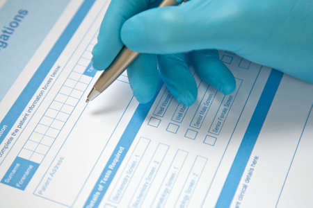 Health professional with blue gloves, completing pathology blood test request form.