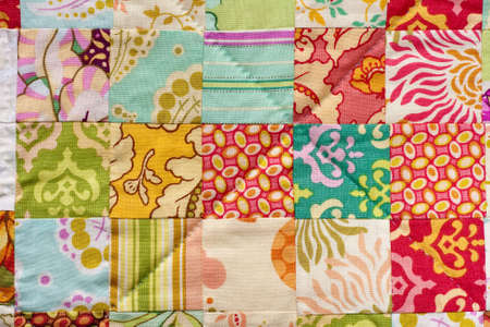 Detail from a handmade patchwork quilt made with squares.