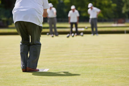 Men playing lawn bowls. Very narrow depth of field. Focus on player.