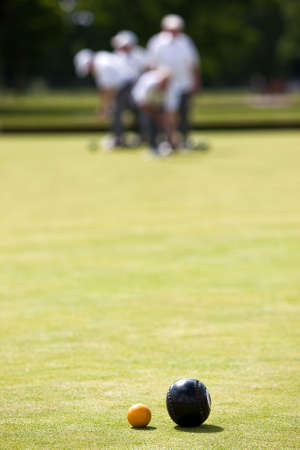 Men playing lawn bowls. Very narrow depth of field. Bowl has stopped near to the jack.