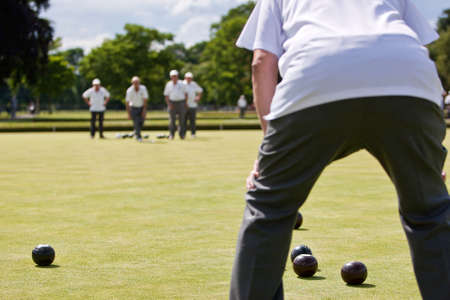 wood lawn: Men playing lawn bowls. Very narrow depth of field. Focus on the woods.
