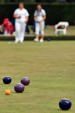 bowling: Ladies playing lawn bowls - focus on the jack.