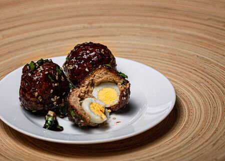 Meat balls with quail egg inside, on a black background