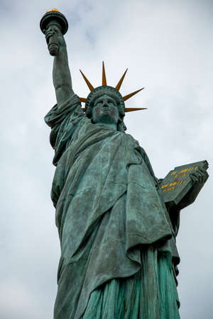 A close up photo of one of the oldest replicas of the Statue of Liberty. This one is quarter the size of the original and is located in Isle of the Swan on Seine river, Paris France.