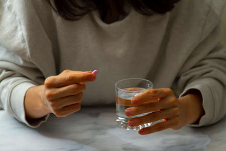 A woman is seen as she is holding a pill in one hand and a glass of water on the other hand. She is about to take the pill. A versatile image for multi purpose use in healthcare related issues.
