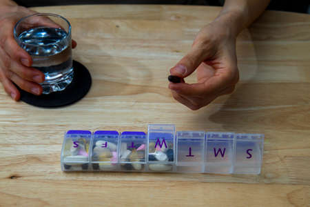 Close up image of a woman's hands as she reaches out to a pill box where she has a variety of medications for each day.  Useful demonstration for chronic diseases, multi drug or supplement use.
