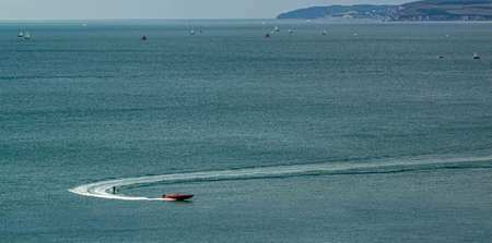 Aerial view of a  red speed boat  sailing fast with someone water skiing at the back in Poole bay, UK There are numerous ships in the bay with scenic cliffs in background. Stock Photo