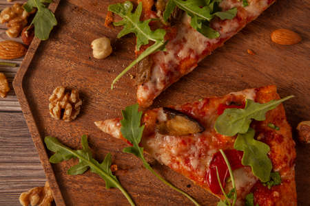 Flat lay close up image of vegetarian cheese and tomato pizza decorated with fresh arugula leaves and grilled egg plants slices. It is served on wooden tray with hazelnuts, almonds and walnuts