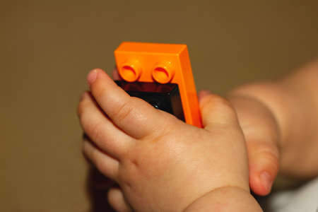 Close up image of an infant baby's hands as he or she is trying to put together blocks. Image is useful to demonstrate motor development, fine motor skills, balance, precision, baby growth themes
